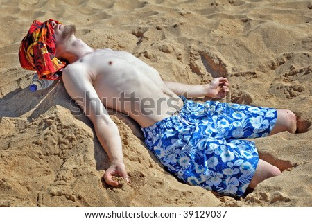 Young man lying on a beach - stock photo