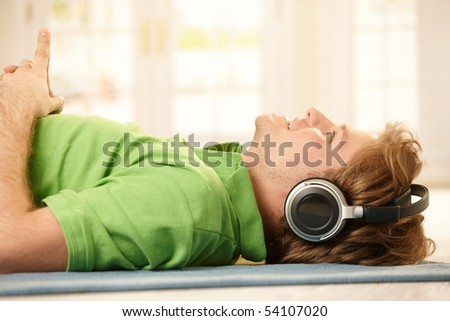 Young man lying on floor wearing headphones, pointing up, smiling. - stock photo