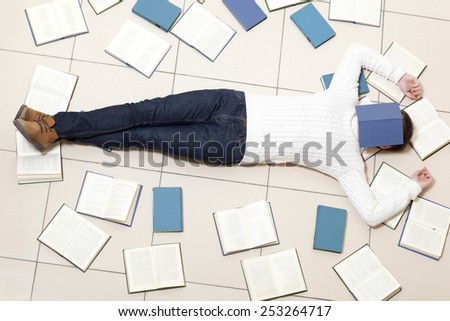 Young man lying on floor with books and reading, top view.  - stock photo