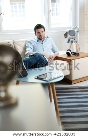 Young man lying on sofa at home, relaxing. - stock photo