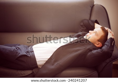 Young Man Lying on Sofa Relaxing with Hands Behind Head Looking Off Into Space as if Daydreaming - stock photo