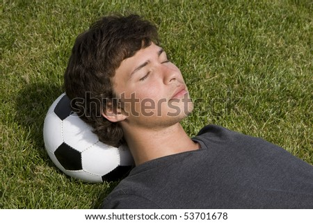 Young man lying on the grass over a soccer ball - stock photo