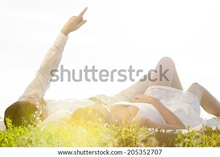 Young man lying with girlfriend while pointing against clear sky - stock photo