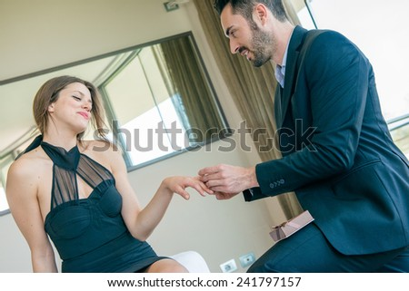 Young man making a marriage proposal to his girlfriend in hotel. - stock photo