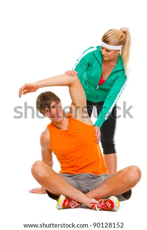 Young man making exercises on floor under the supervision of personal trainer - stock photo