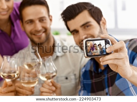 Young man making self portrait of his friends by digital camera. - stock photo