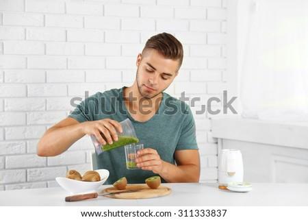 Young man man pouring fresh kiwi juice into glass - stock photo