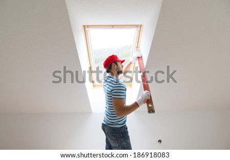 Young man measuring the wall of new home with level - stock photo
