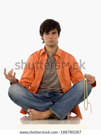 Young man meditating. - stock photo