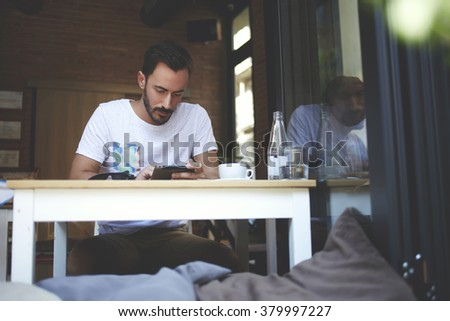 Young man modern businessman concentrated reading news in network via touch pad while sitting in his restaurant, successful male watching video on digital tablet while waiting for order in luxury cafe - stock photo