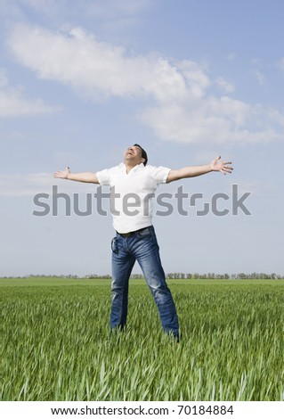 young man moves in a green field of grass to meet the sun - stock photo