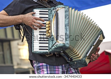 Young man musician playing the accordion - stock photo