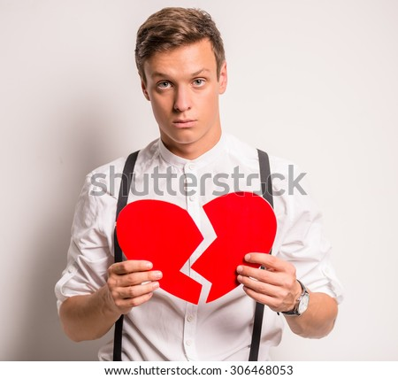 Young man on a gray background holding paper broken heart - stock photo