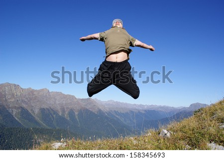 Young man on a mountain slope in the jump - stock photo
