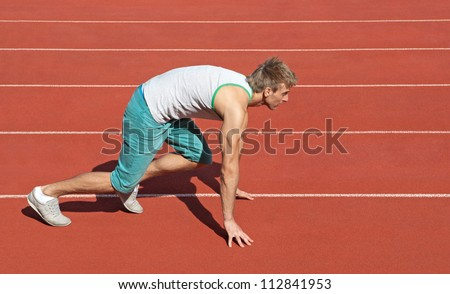 Young man on a racetrack preparing to run. - stock photo