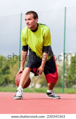 Young man on basketball court dribbling with ball. Streetball, training, activity. Real and authentic - stock photo