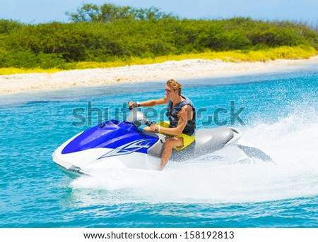Young Man on Jet Ski, Tropical Ocean, Vacation Concept - stock photo