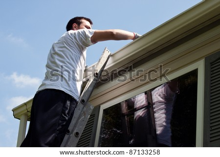 Young man on latter cleaning house gutters - stock photo