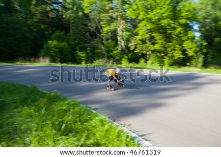 Young man on rollerblades skating at park - stock photo