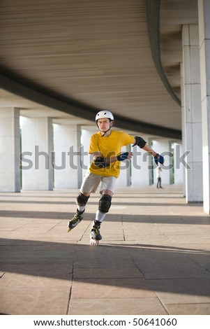 Young man on rollerblades skating in some urban place - stock photo