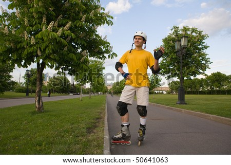 Young man on rollerblades standing at park - stock photo