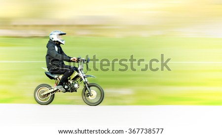 Young man on small motorbike or moped in blurred motion - stock photo