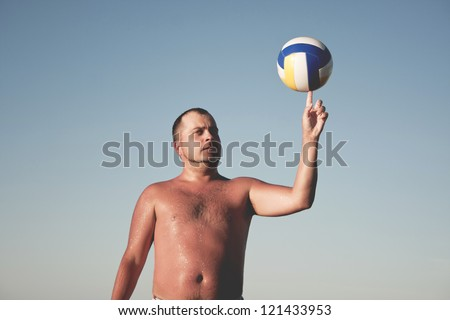 Young man on the beach playing in his vacation, he is balancing the ball on his fingertip - stock photo