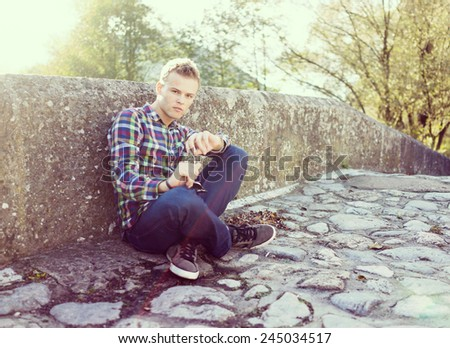 Young man on the old stone bridge with harsh sunlight in background - stock photo
