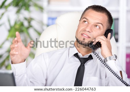 Young man on the phone. He is looking for a job. - stock photo