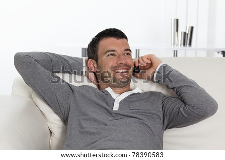 young man on the phone on sofa - stock photo