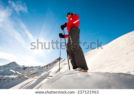 Young man on top of a mountain ready for skiing - stock photo