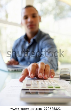 Young Man On Using Calculator At Home - stock photo