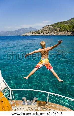 Young man on vacation jumping from a boat in turkey, enjoying his freedom, while on a summer holiday - stock photo