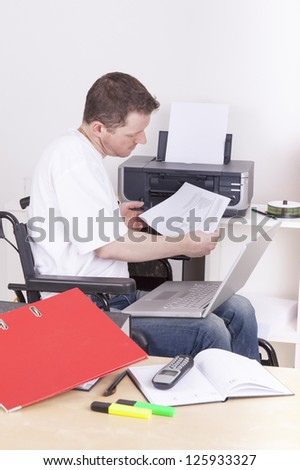young man on wheelchair working in a office, using a laptop computer - stock photo