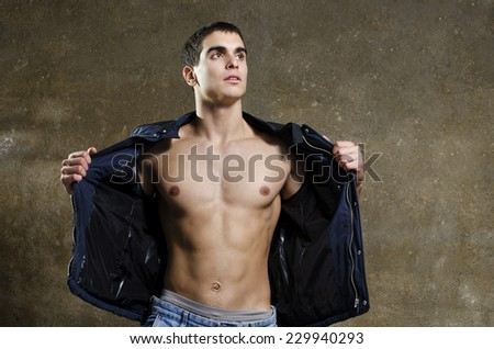 Young man opens his jacket and shows his muscles on dirty wall background - stock photo