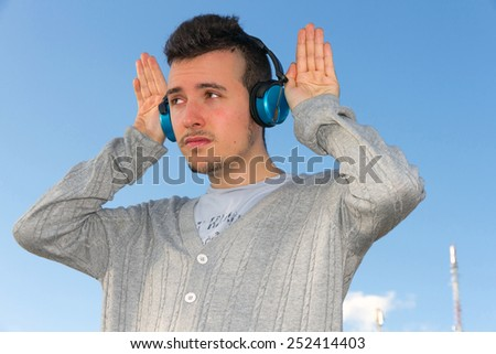Young man outdoors with headphones or earphones sound, hands and ears or receiving parabolic antennas and telecommunications towers the bottom  - stock photo