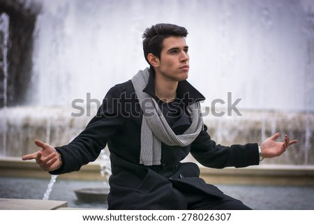 Young Man Outside Sitting Next to Big Fountain, with Arms Spread Open and Confident Expression - stock photo