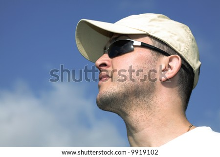 Young man over sky background, copy space on the left. - stock photo