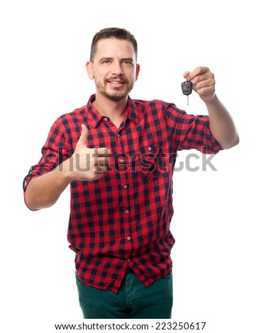 Young man over white background. Holding a car keys with his thumb up also - stock photo