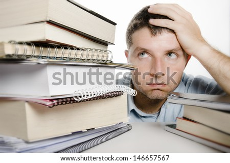 Young Man Overwhelmed and frustrated among a pile of books and notebooks on the desk - stock photo