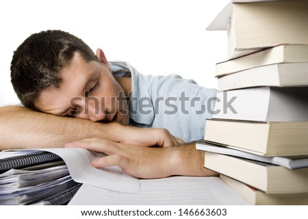 Young Man Overwhelmed and tired sleeping over the pile of books and notebooks on the desk - stock photo