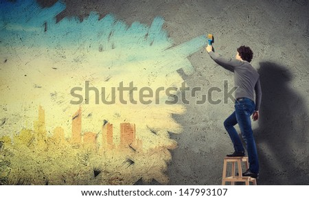 Young man painting a yellow colour cityscape on the wall - stock photo
