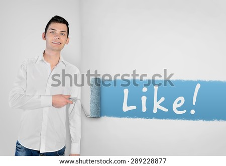 Young man painting Like word on wall - stock photo