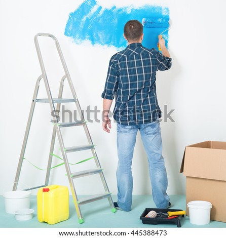 Young man painting wall at home - building and home concept - stock photo