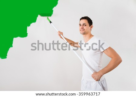 Young man painting wall with green paint roller at home - stock photo