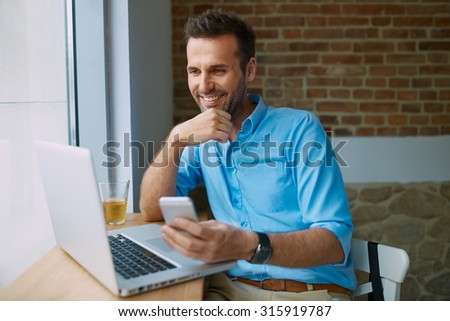 Young man paying for online shopping with smartphone - stock photo