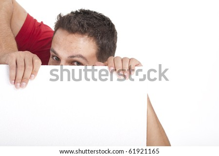 young man peeking behind empty white billboard - stock photo