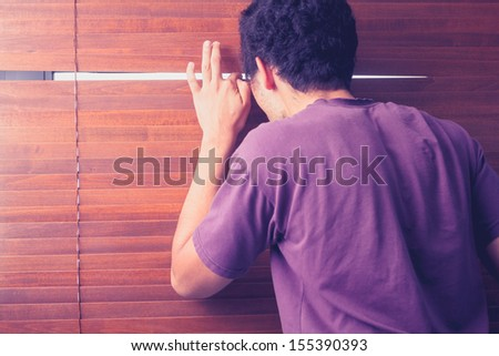 Young man peeping out through venetian blinds - stock photo