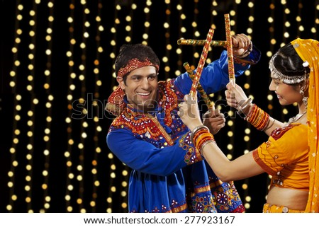 Young man performing Dandiya Rass with woman against neon lights - stock photo
