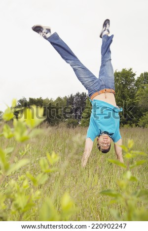 Young man performing handstand in meadow - stock photo